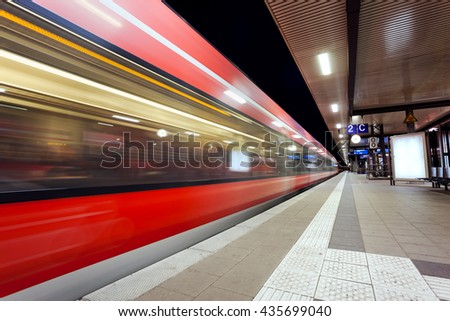 Modern railway station with high speed passenger train on railroad track in motion at night  in Nuremberg, Germany. Fast blurred red commuter train.. Colorful industrial landscape