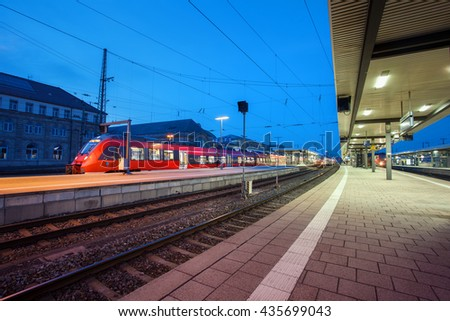 Modern railway station with passenger train on railroad track at night  in Nuremberg, Germany. Fast red commuter train.. Industrial landscape