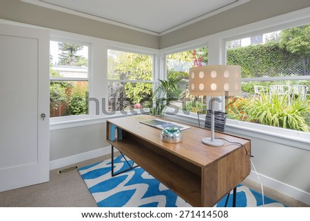 Modern rectangle wooden desk and desk lamp in glass house style home office surrounded by green garden. Work-space table standing on blue zig zag pattern rug. - stock photo