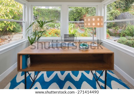Modern rectangle wooden desk and table lamp in glass house style home office surrounded by green garden. Work-space table standing on blue zig zag pattern rug. - stock photo