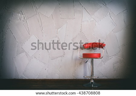 modern red chair in an empty room. in the circle of light there is red swivel bar stool on a background of gray wall with decorative relief plaster. copy space for your text - stock photo