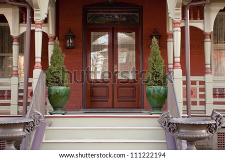 Modern red house and porch. Green shrubs in green vases outside. - stock photo