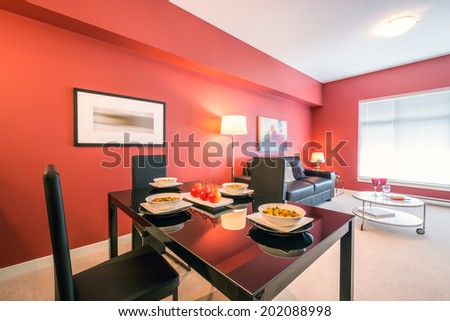 Modern red kitchen with a living room in a luxury apartment. Interior design. - stock photo