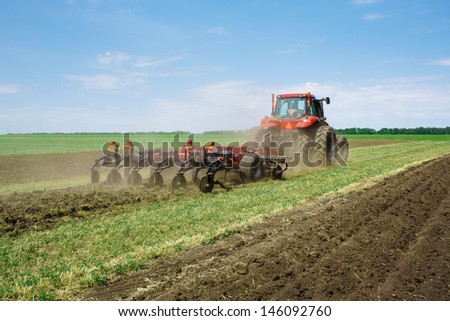 modern red tractor in the agricultural field; mechanism. Tractor plowing land.  Harvester sowing wheat. - stock photo