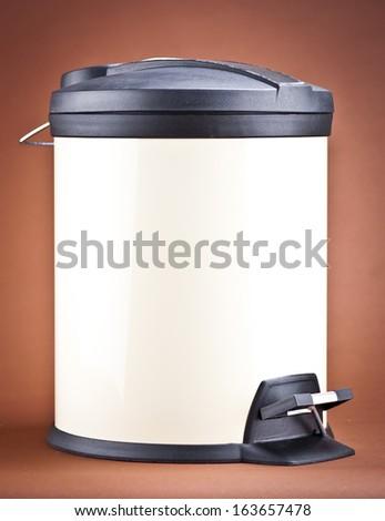 Modern refuse bin on a brown background - stock photo