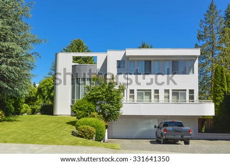 Modern residential house with car parked on driveway in front. Big family house with double garage, lawn in front, and blue sky background. British Columbia, Canada. - stock photo