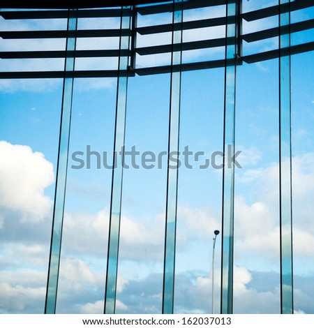 Modern residential window with blue sky and white clouds.