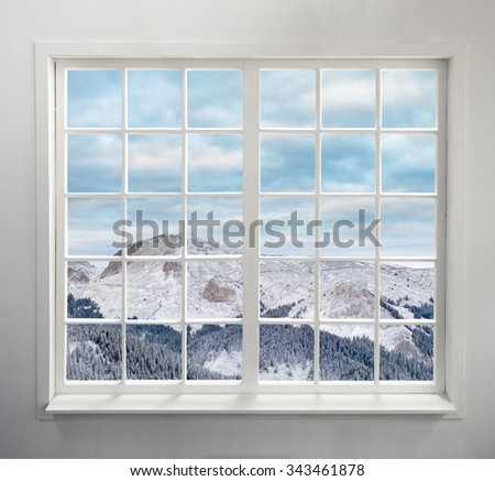 Modern residential window with snowy mountain and clouds - stock photo