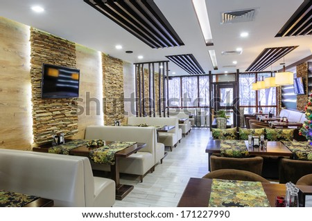 Modern restaurant interior with tables and sofas - stock photo