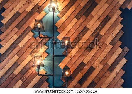 Modern restaurant with rustic decorative elements. Interior design details with lamps and bulb lights. Wooden wall decoration with vintage looking lights - stock photo