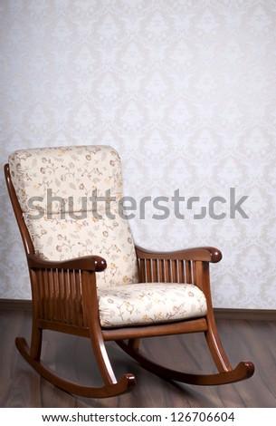 modern rocking chair near a light wall - stock photo