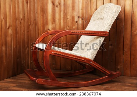 Modern rocking-chair on wooden wall background - stock photo