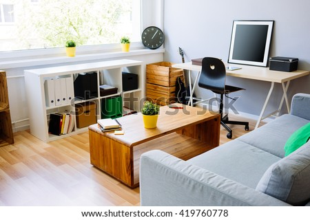 Modern room, home office interior. Room with sofa, desk, chair, small table and other furniture - stock photo
