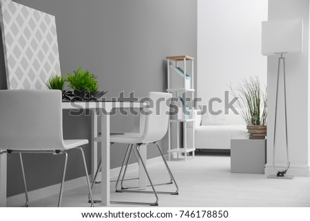 Modern room interior with white chairs and table