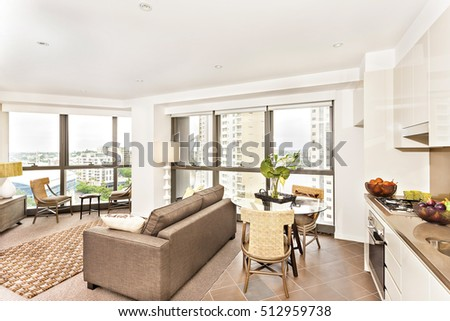 Modern room view near kitchen with sofa set, luxury living room with glass table and sofa, oven and gas cooker have attached to the pantry cupboard, flower pot on the table, chairs are wooden.