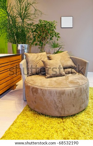 Modern round sofa on a carpet in interior - stock photo