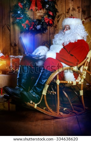 Modern Santa Claus at his wooden house surfing in the Internet with his laptop. Christmas. - stock photo