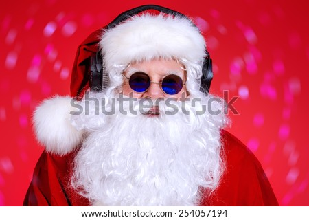 Modern Santa Claus in headphones and sunglasses. DJ, party. Christmas celebration.