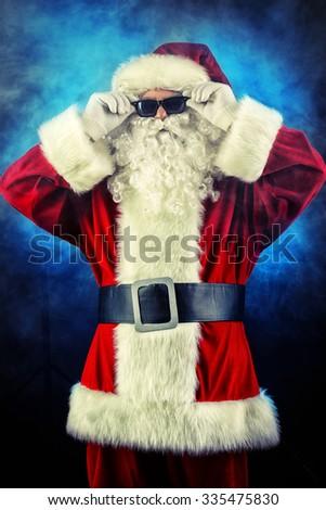 Modern Santa Claus in sunglasses over dark background. Christmas.  - stock photo