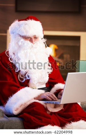 Modern Santa Claus sitting by fireplace using computer computer.? - stock photo