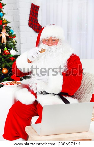 Modern Santa Claus sitting on sofa and using computer  - stock photo