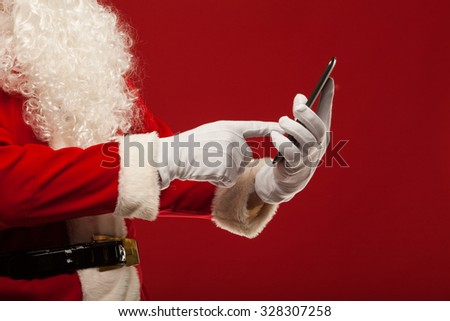 Modern Santa Claus using tablet pc over red background. Christmas. - stock photo