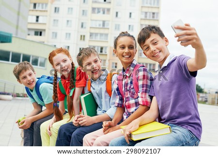 Modern school learners making selfie outside
