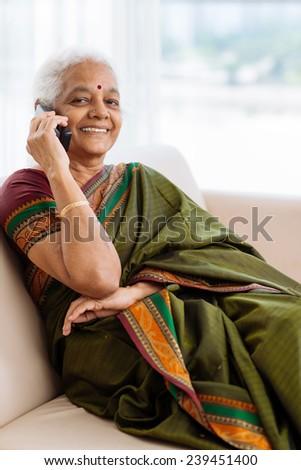 Modern senior Indian woman talking on the phone - stock photo