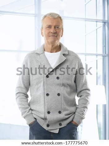 Modern senior man standing  in office. - stock photo