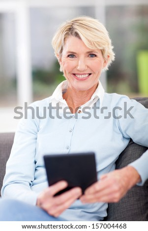 modern senior woman with tablet computer at home - stock photo