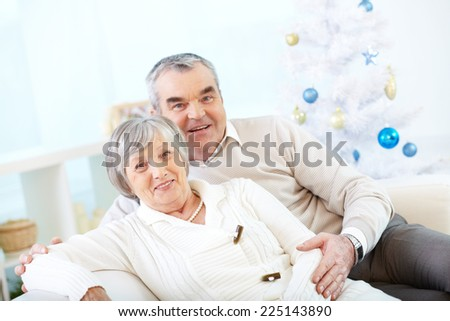 Modern seniors in casual looking at camera on background of decorated Christmas tree - stock photo