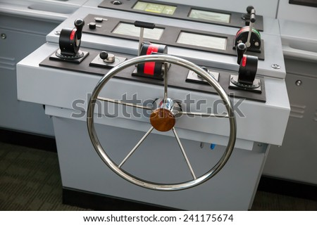 Modern ship control panel with steering wheel and engine accelerators, captains bridge - stock photo