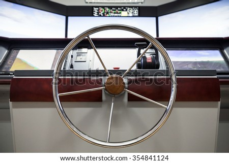 Modern ship control panel with steering wheel and engine accelerators on the captain bridge - stock photo