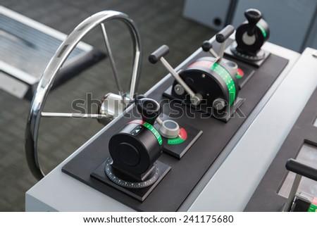 Modern ship control panel with steering wheel, captains bridge - stock photo