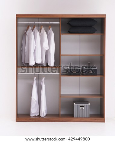 modern shirts and dress hanging on rail in wooden wardrobe at home - stock photo