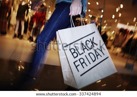 Modern shopper with Black Friday paperbag going in the mall - stock photo