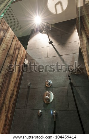 modern shower faucet with dark tiled wall and printed wood glass dividers