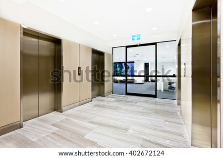 Modern silver elevator in a luxury building with closed glass door to another area - stock photo