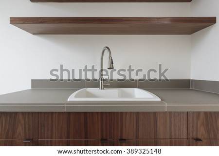 Modern sink with chrome fixtures with a shelf - stock photo