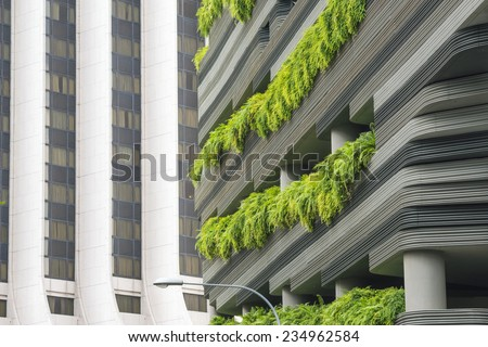 modern skyscraper wall with green plants terraces in Singapore city - stock photo
