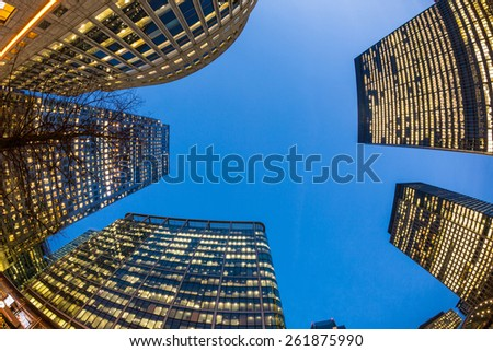 Modern skyscrapers in London at sunset, bottom view. Image taken at blue hour in Canary Wharf, financial district of the city, with a fish eye lens. - stock photo
