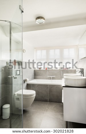 Modern small bathroom interior with bright walls and dark tiles