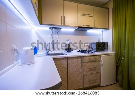 Modern small kitchen with green curtains and LED backlight