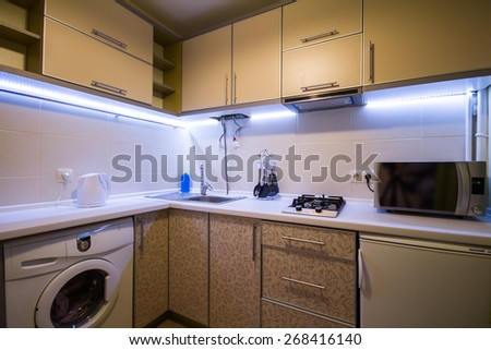 Modern small kitchen with green curtains and LED backlight - stock photo