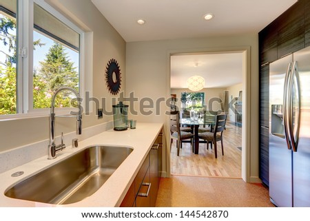 Modern small new kitchen with large sink and white countertops.