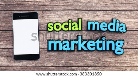 "Modern smart phone on a wooden table near ""social media marketing"" slogan. - stock photo"