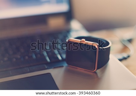 Modern smart wrist watch laying on a notebook. Trending new technology that lets you always stay connected to the internet and media. Never miss a message.Blue hipster toning - stock photo