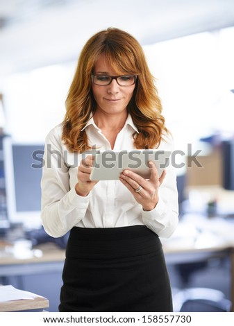 Modern, smiling businesswoman holding tablet in the office - stock photo