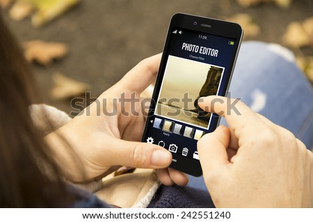 modern social photography concept: young woman using photo editor app on the smartphone at the park - stock photo