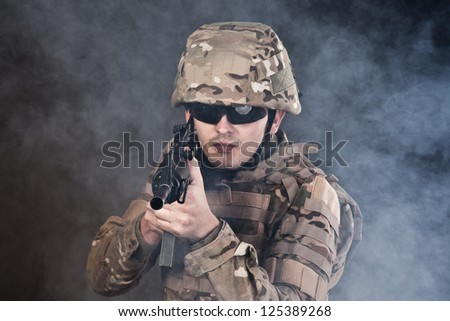 Modern soldier with rifle isolated on a black background - stock photo